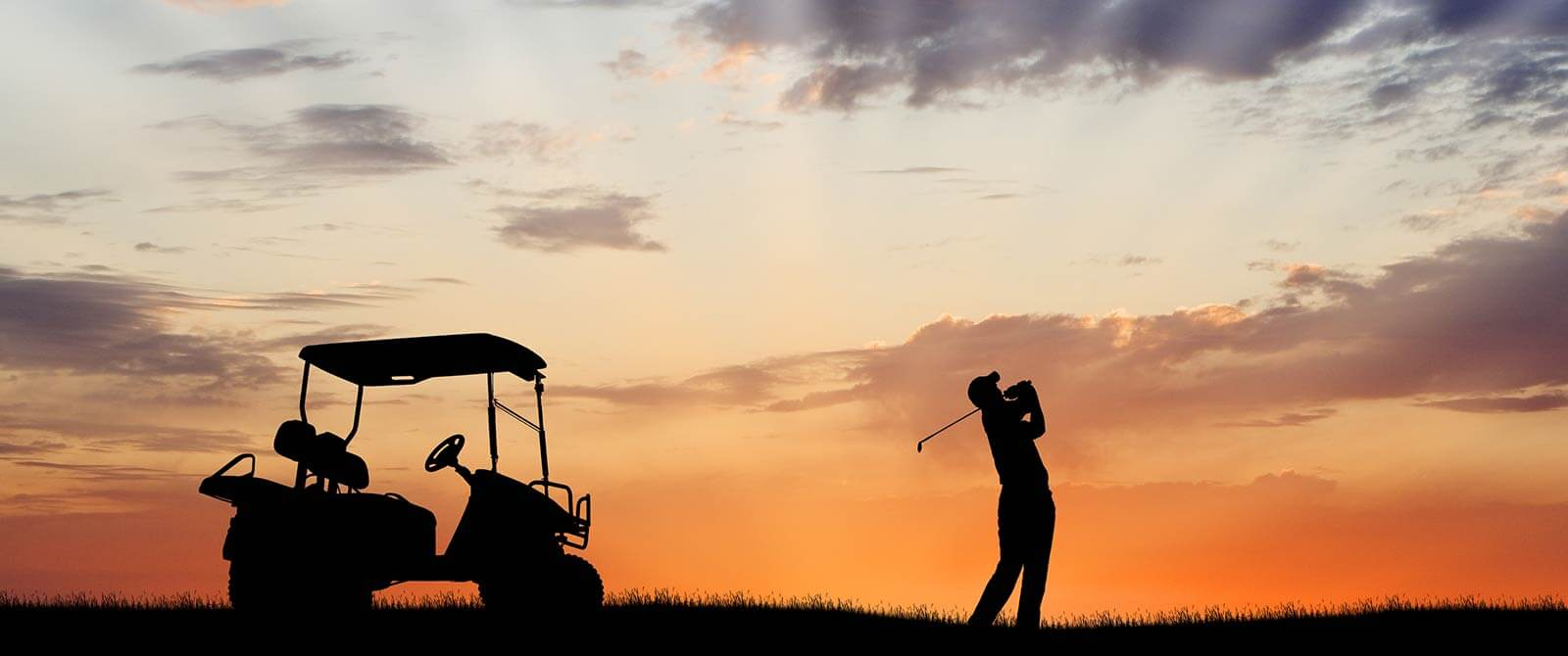 Silhouette of a man playing golf next to his lithium-iron powered golf buggy