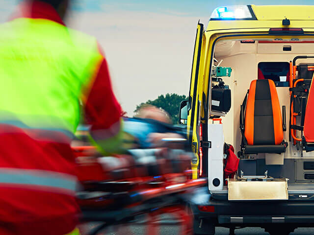Emergency services attendants pushing a patient to their ambulance